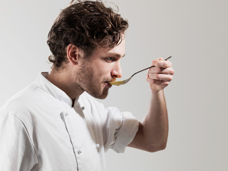 Chef Tasting Food From Spoon Against White Background