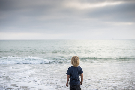 Rear View Of Boy Gazing Out To Sea, Dana Point, California, Usa