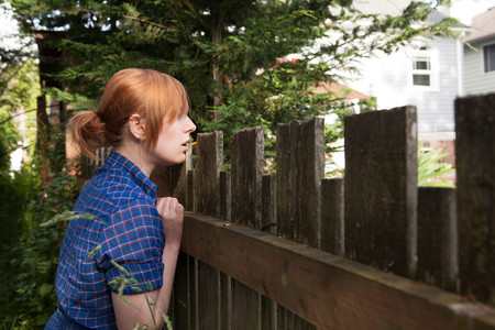 Young Woman Looking Over Fence To Neighbor's Yard