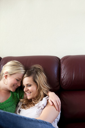 Young Lesbian Couple Embracing On Couch