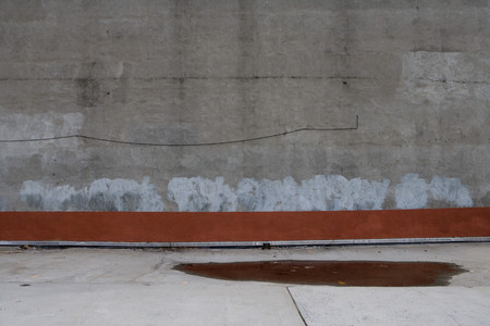 Sidewalk And Wall With Puddle