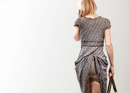 Donna con vestito catturata in biancheria intima usando il cellulare, ripresa in studio Archivio Fotografico