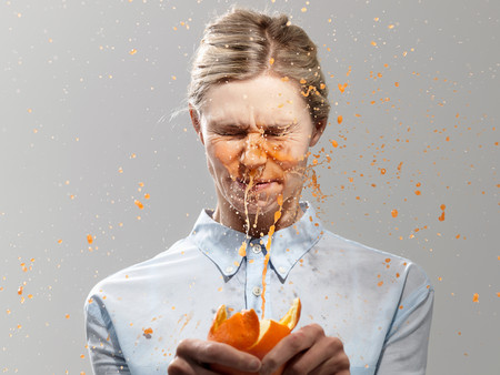 Woman Splashed With Juice From Orange, Studio Shot