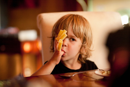 Boy Eating Pasta Off Fingers Stock Photo