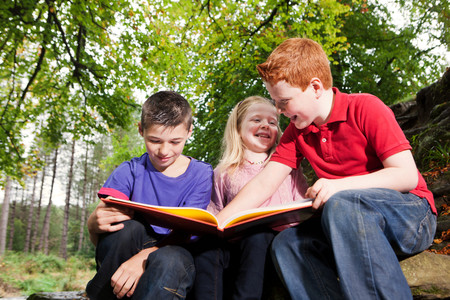 Three Children Looking At A Book Together