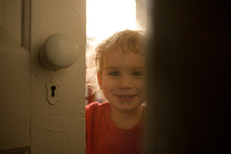 Toddler Boy Looking Through Gap In Door