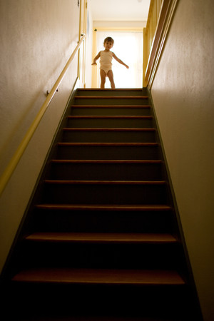 Young Girl Standing At Top Of Stairs