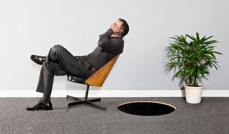 Business Man Tilting Backwards On Chair Towards Hole In Floor