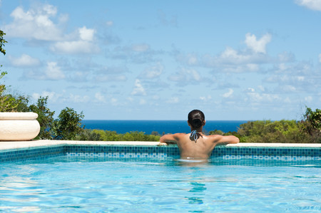 Rear View Of Young Woman In Swimming Pool, Looking At View 版權商用圖片