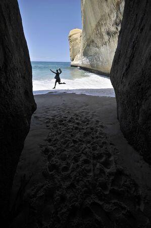 Woman Jumping On Beach, New Zealand