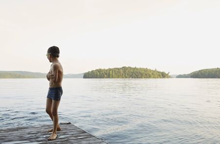 Boy Looking Out At Lake From Wooden Pier, Ontario, Canada