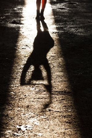 Feet And Shadow Of Young Woman Dancing In Sunlit Underpass