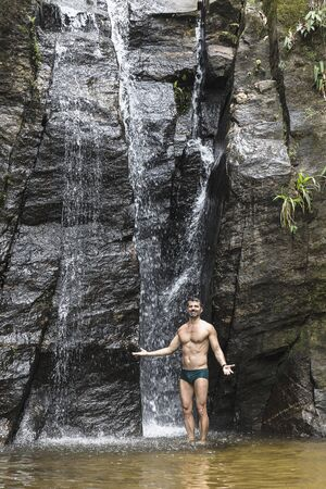 Portrait Of Mature Man With Open Arms In Front Of Waterfall, Tijuca Forest, Rio De Janeiro, Brazil
