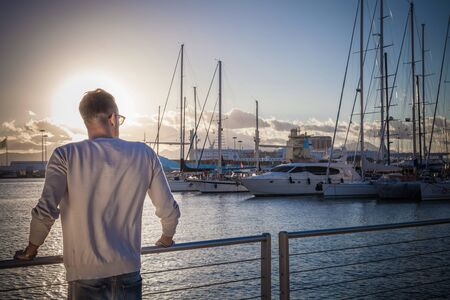 Young Man Relaxing By Port, Cagliari, Sardinia, Italy