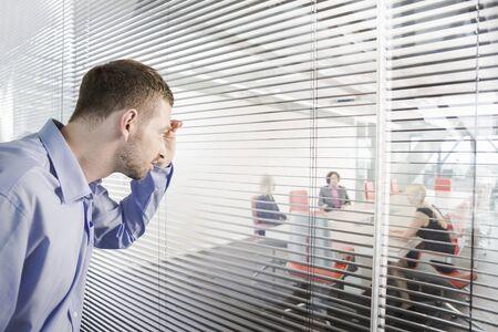 Man Peering Through Window Blinds