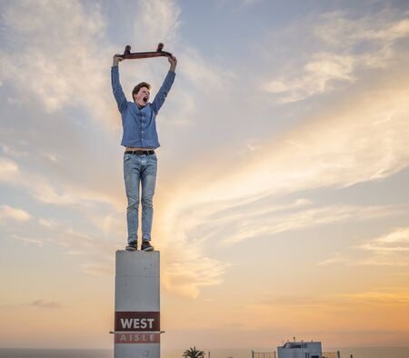 Portrait Of Young Man Standing On Pillar Holding Skateboard Above Head Stockfoto