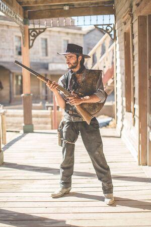 Porträt von Cowboy hält Schrotflinte auf Wild-West-Filmset, Fort Bravo, Tabernas, Almeria, Spanien Standard-Bild