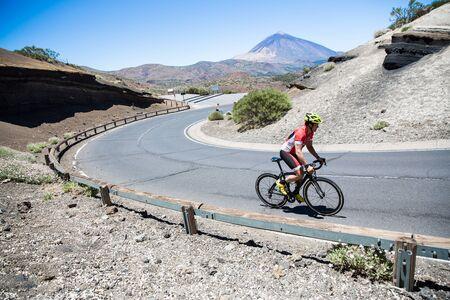 Ciclista maschio in bicicletta su strada tortuosa, Tenerife, Isole Canarie, Spain