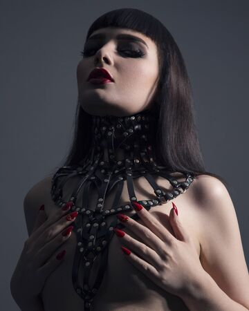 Portrait Of Young Woman Wearing Ornate Leather Necklace, Covering Naked Breasts With Hands Stock Photo