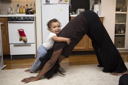 Mujer adulta media ejercitarse sobre una alfombra con su hija pequeña Foto de archivo