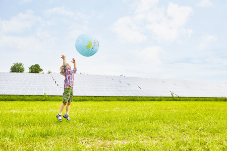 Young Boy Playing With Inflatable Ball, On Field, Next To Solar Farm