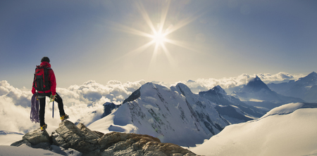 Panoramic View Of Male Climber Looking Out From Snow Covered Mountain Top, Swiss Alps, Switzerland Stock fotó