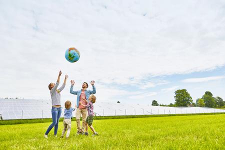Junge Familie spielt mit aufblasbarem Ball, auf dem Feld, neben Solarpark