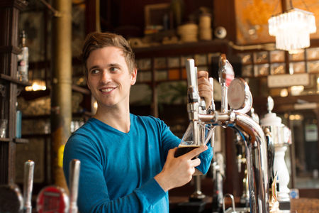 Young Man Working In Public House, Serving Drink Stock Photo