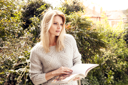 Mid Adult Woman In Garden Reading Cookery Book