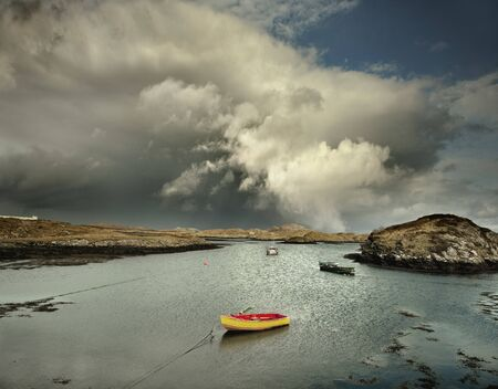 Boats Moored In Natural Sea Harbor With Storm Clouds, Isle Of Barra, Hebrides, Scotland, Uk Foto de archivo