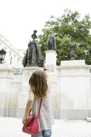 Young Girl Taking Picture Of Queen Mother Statue With Smartphone