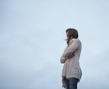 Low Angle View Of Woman With Arms Folded And Overcast Sky