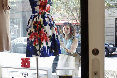 Mature Woman Looking In Window Of Fashion Boutique