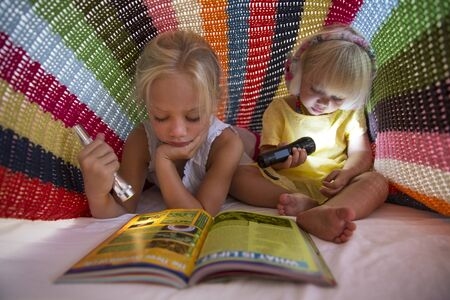 Girl And Toddler Sister Lying On Bed Hiding Under Blanket And Using Torch To Read Magazine