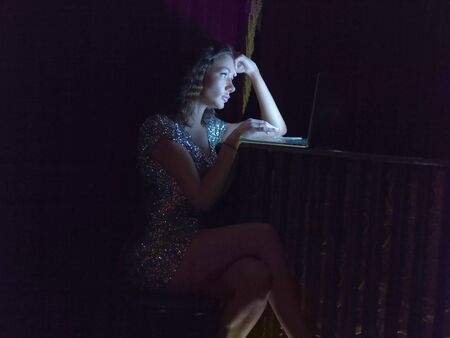 Mid Adult Woman Sitting In Bar, At Night, Using Laptop Stock Photo