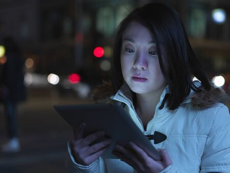 Young Woman In Street, At Night, Using Digital Tablet