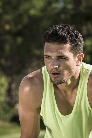 Portrait Of Sweaty Young Man Training In Park Stock Photo