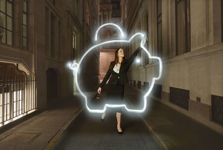 Businesswoman Light Painting Glowing Piggy Bank Symbol On City Street At Night