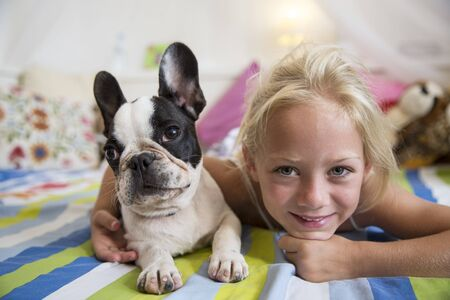 Portrait Of Girl And Cute Dog Lying On Bed