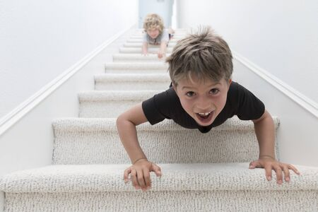 Portrait Of Two Brothers Crawling Headfirst Down Stairs