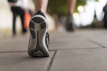 Close Up Of Male Runners Trainers Running On Sidewalk