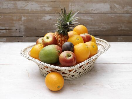 Basket Of Fresh Fruit On Wooden Table