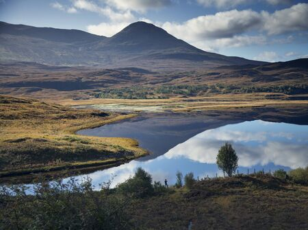 Man Photographing Reflection Of Mountain In Loch, Highland, Scotland