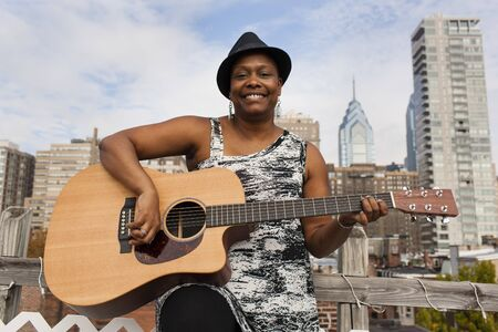 Portrait Of Happy Mature Woman Playing Guitar In Front Of Philadelphia Skyline, Usa