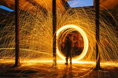 Man Creating Circular Golden Spark Light Trails In Derelict Building