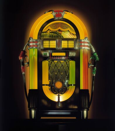 Illuminated Vintage Jukebox With Attached Gas Pump Nozzles Stockfoto