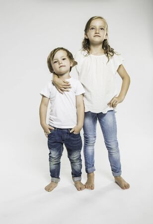 Studio Portrait Of Confident Girl With Arm Around Her Brother