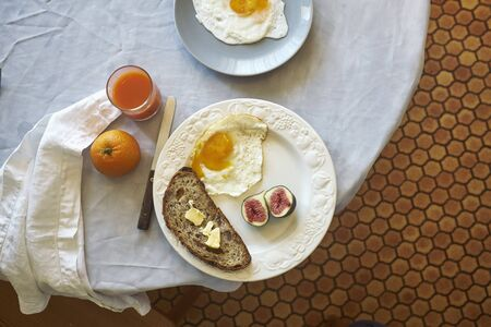 Overhead View Of Breakfast Table With Plate Of Fried Egg And Figs