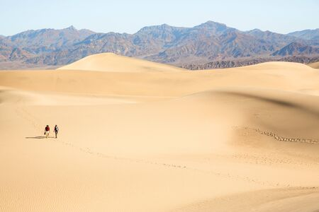 Two People Walking Across Sand, Death Valley, California, Usa Imagens