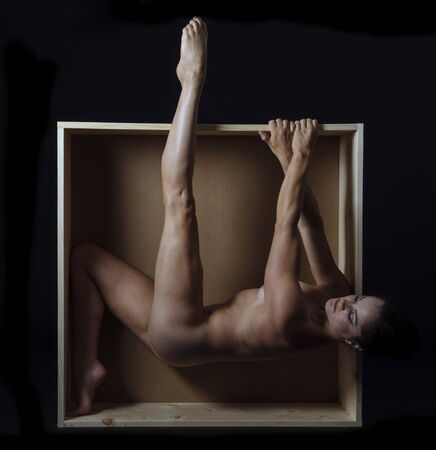 Naked Woman Hanging From Edge Of Box 版權商用圖片